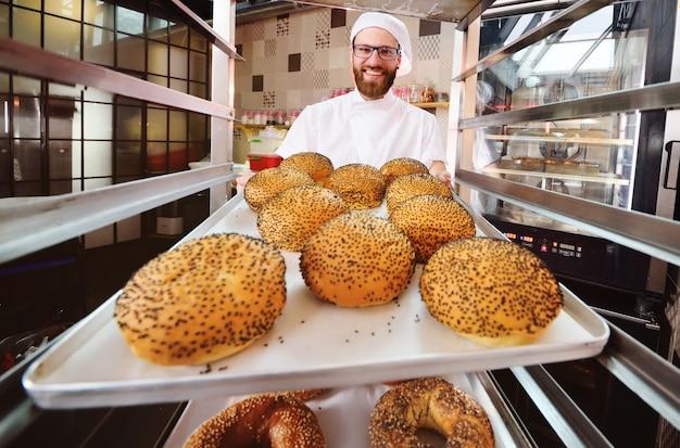 Hermoso baker en uniforme blanco sosteniendo una bandeja con pasteles frescos de una panadería o fábrica de pan