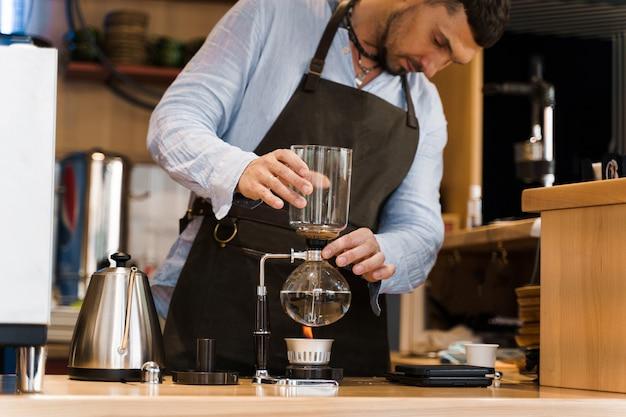 Hermoso barista barbudo sostiene el dispositivo de sifón en las manos antes de preparar el café en la cafetería