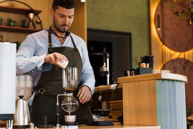 Hermoso barista barbudo vierte café recién molido al dispositivo de sifón para preparar café en la cafetería