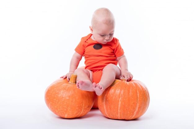 Hermoso bebé en camiseta naranja sobre un fondo blanco.