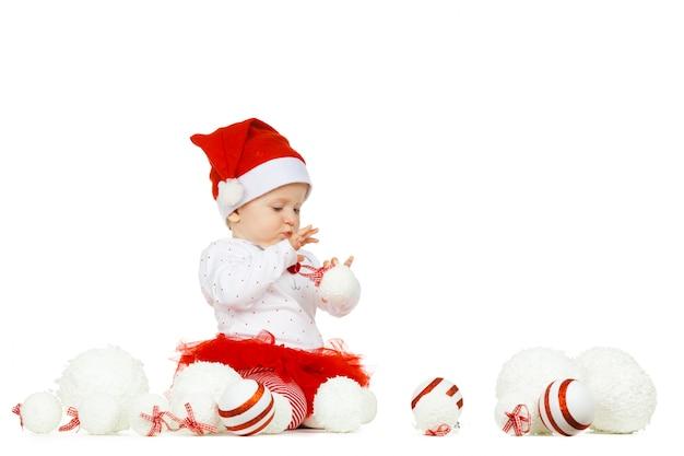 Hermoso bebé gracioso en un sombrero de navidad aislado en blanco