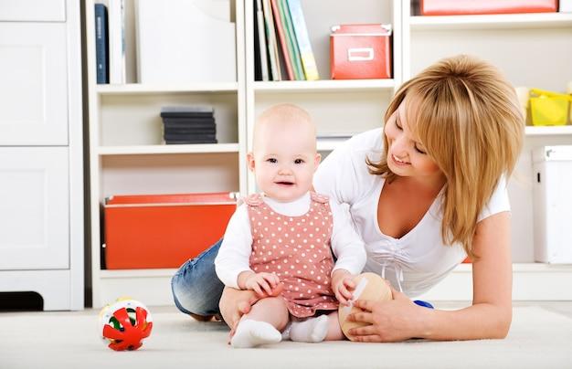 Hermoso bebé jugando con juguetes con madre feliz en el interior