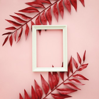 Hermoso borde rojo deja sobre fondo rosa con marco en blanco