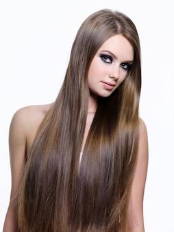 Hermoso cabello liso largo y liso de mujer joven, aislado sobre fondo blanco.