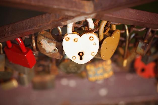 Hermoso candado en forma de corazón blanco bloqueado en cadena de hierro, concepto de romance