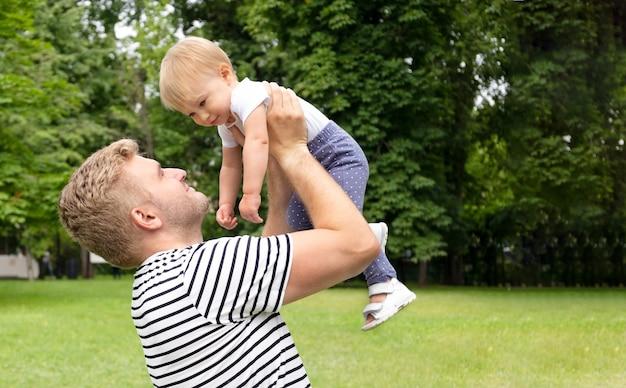 Hermoso, caucásico, hombre, tenencia, rubio, niña, aproximadamente, 1 año de edad, sonriente, juego, game., pasar, tiempo libre, con, family., idea, de, niño, y, papá, relación, diversión, con, niño, familia feliz, exterior, espacio de copia
