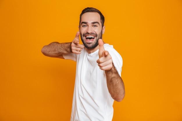 Hermoso chico en camiseta apuntando con el dedo mientras está de pie, aislado en amarillo