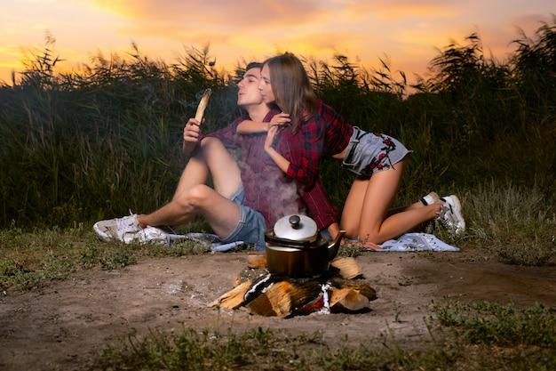 Un hermoso chico y una chica con camisas rojas a cuadros, soplando sobre un palo de fumar con el que viene el humo ...