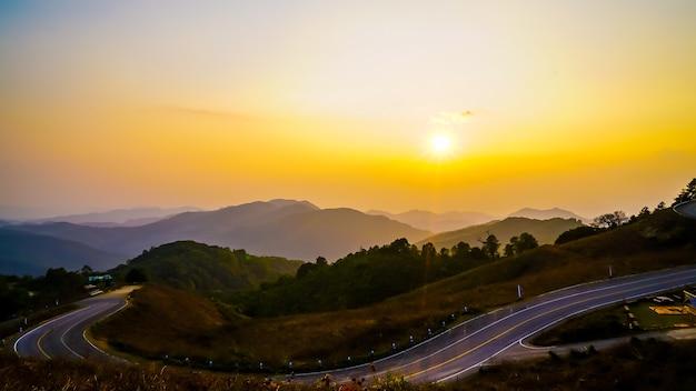 Hermoso cielo al atardecer con capa de montaña y carretera