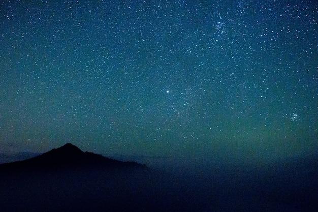 Hermoso cielo azul estrellado por la noche con el telón de fondo de las montañas