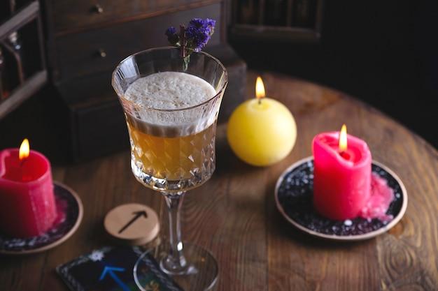 Hermoso cóctel amargo alcohólico amarillo con flores secas y runas en estilo bruja oscura