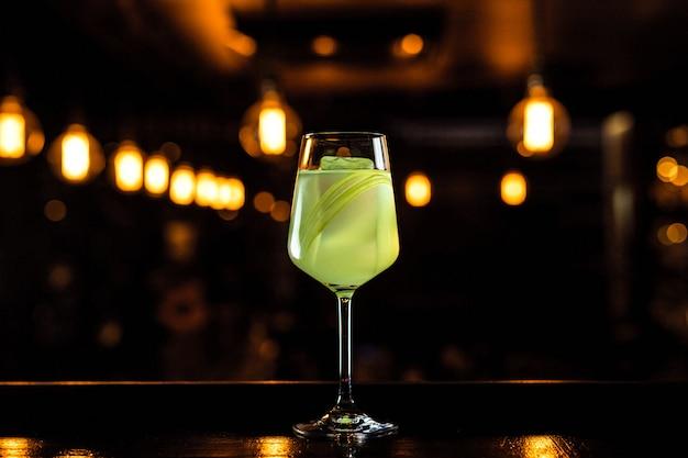 Un hermoso cóctel verde claro con apio en una copa de vino, luces bokeh, enfoque selectivo, horizontal
