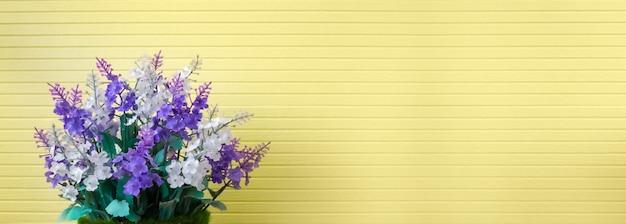 Hermoso color púrpura lavanda o lila ramo de flores de plástico artificial en un bonito jarrón sobre fondo de textura de papel tapiz amarillo con textura de rayas en el spa del hogar