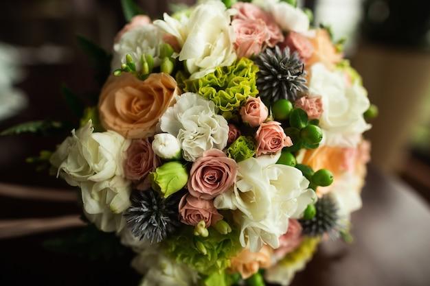 Hermoso y colorido ramo de novia sobre mesa de madera
