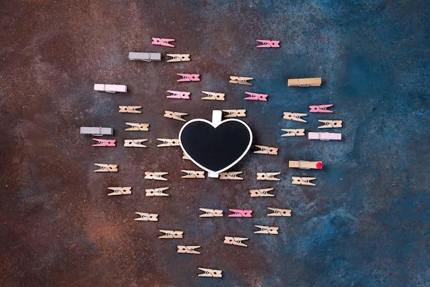 Hermoso corazón hecho de pinzas para la ropa con un tablero de tiza