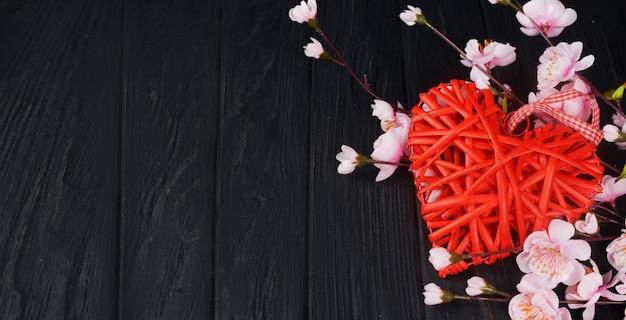 Hermoso corazón rojo de mimbre con flores rosadas sobre un fondo negro