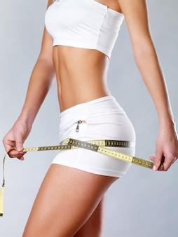 Hermoso cuerpo de mujer con cinta métrica. cocnept de estilo de vida saludable.