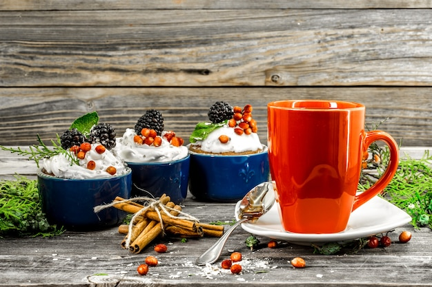 Hermoso cupcake de navidad con crema y bayas en la mesa de madera conos de canela
