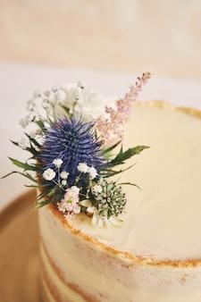Hermoso y delicioso pastel con flores y bordes dorados sobre una superficie blanca