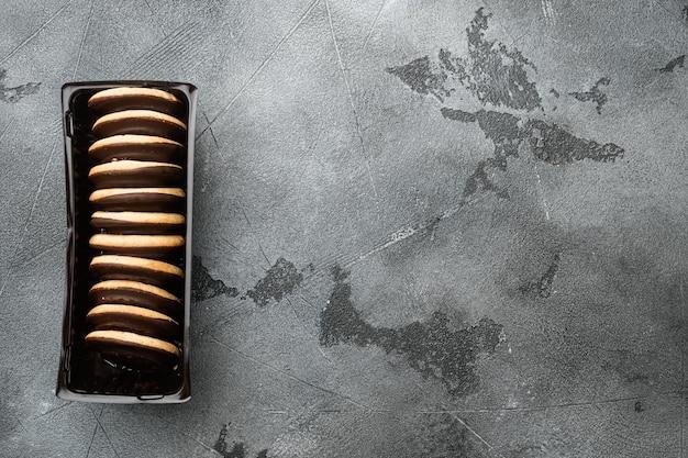 Hermoso y delicioso pastel mordido de masa de galleta con mermelada, en recipiente de bandeja de plástico, en recipiente de bandeja de plástico, sobre fondo gris, vista superior plana, con espacio para copiar texto