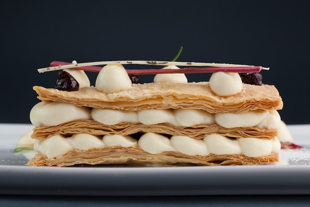 Hermoso y delicioso postre milhojas con mascarpone y bayas en un plato blanco con salsa, hermosa oferta de restaurante