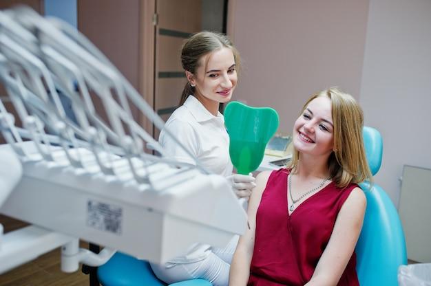 Hermoso dentista mostrando los dientes nuevos de su paciente a través del espejo en el gabinete dental.