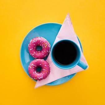 Hermoso desayuno con donas y una taza de café en amarillo