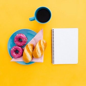 Hermoso desayuno con donas y taza de café con cuaderno en amarillo