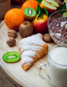Hermoso desayuno frutas de leche, pan y croissant.