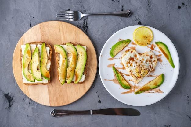 Un hermoso desayuno romántico saludable de huevos fritos en forma de corazón en un plato blanco y sándwiches de aguacate