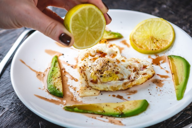 Un hermoso desayuno romántico saludable de huevos fritos en forma de corazón con rodajas de aguacate y limón