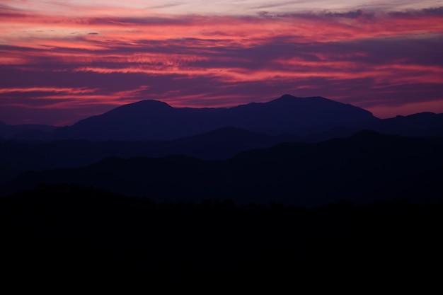 Hermoso diseño de cielo violeta y rojo con montañas