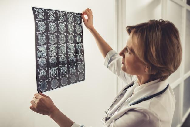 Hermoso doctor en bata blanca está examinando imágenes de rayos x.