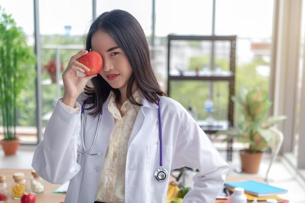 Hermoso doctor está mostrando fruta en la oficina.