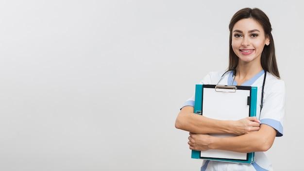 Hermoso doctor sosteniendo una carpeta con espacio de copia