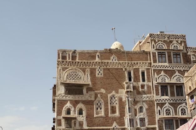 Hermoso edificio antiguo bajo la luz del sol y un cielo azul en sana'a, yemen