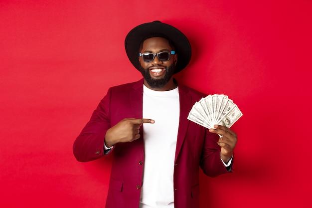 Hermoso y elegante modelo masculino afroamericano mostrando dinero y sonriendo, con gafas de sol y sombrero elegante, de pie sobre fondo rojo.