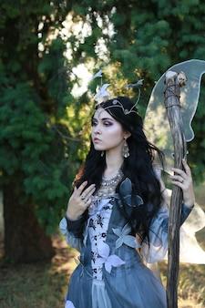 Hermoso elfo místico en elegante vestido de flores en el bosque
