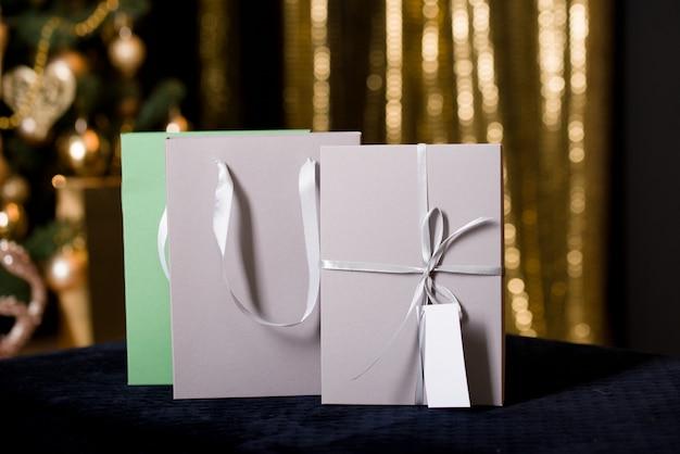 Hermoso embalaje para regalo en tonos de cama de un árbol de navidad con luces doradas.
