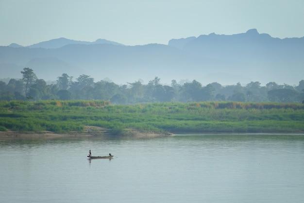 Hermoso escénico en la mañana, pescador trabajando en el río