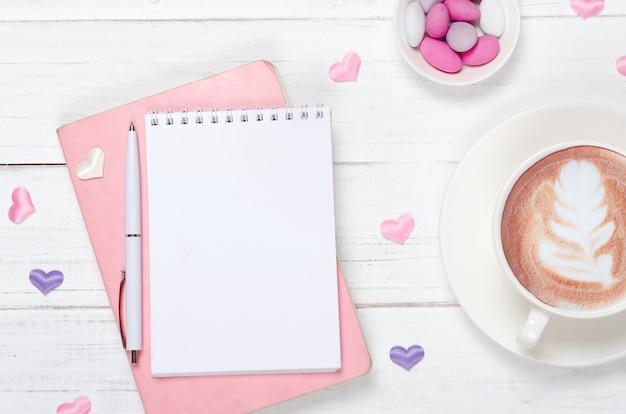 Hermoso escritorio con un bloc de notas, café y decoraciones.