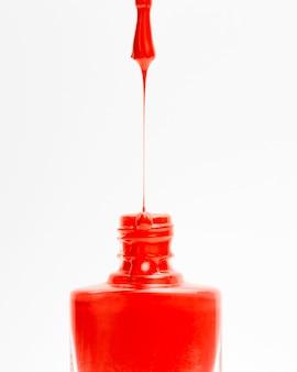 Hermoso esmalte de uñas de color rojo que gotea de pincel en botella sobre fondo blanco