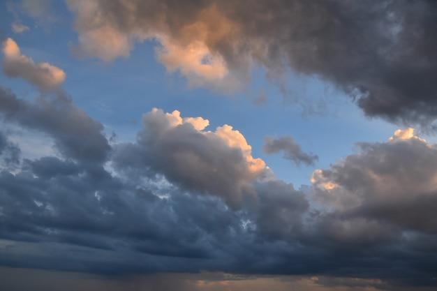 Hermoso y espectacular atardecer temprano con nubes esponjosas ornge iluminadas sobre el cielo azul claro, vista de ángulo bajo