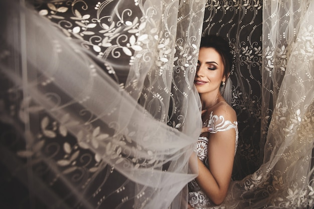 Hermoso estilo de novia. boda niña de pie en el vestido de novia de lujo junto a la ventana