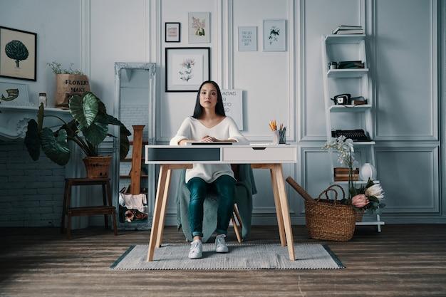 Hermoso y exitoso. mujer atractiva joven mirando a la cámara mientras está sentado en la oficina en casa