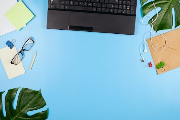 Hermoso flatlay con una computadora portátil, anteojos, hojas de filodendro y otros accesorios de negocios. concepto de una oficina en casa. endecha plana.