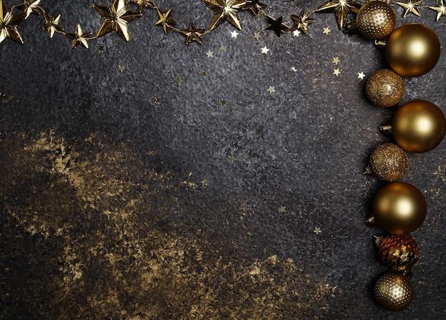 Hermoso fondo oscuro de año nuevo con estrellas y adornos navideños dorados