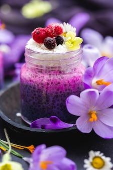 Hermoso frasco de batido vegano púrpura cubierto con bayas, rodeado de flores de primavera