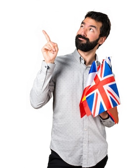 Hermoso hombre con barba sosteniendo muchas banderas y apuntando hacia arriba