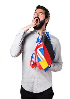 Hermoso hombre con barba sosteniendo muchas banderas y bostezando